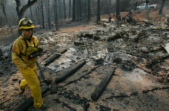 A fire official worked yesterday in Briceburg, Calif. About 2,000 homes faced danger from the flames, while 12 were destroyed.