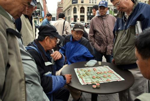 Men under the gateway gather around to play Chinese chess on Beach Street.