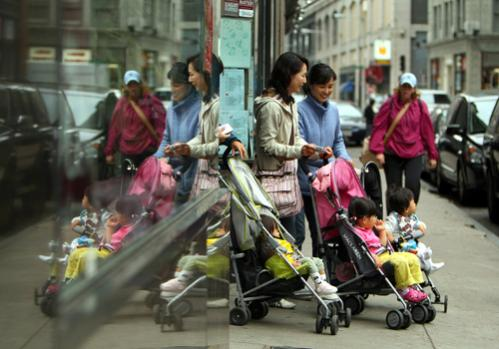 Women leave a restaurant with children in strollers on Essex Street.