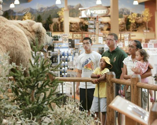 The Pennington family of Colorado view a stuffed animal exhibit at Cabela's in Nebraska recently. A Conference Board report says the slight drop in gas prices may have sparked a little hope among consumers.