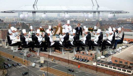 Dinner in the Sky guests are strapped into leather seats, while waiters and waitresses can stand in an aisle at the center of the table.