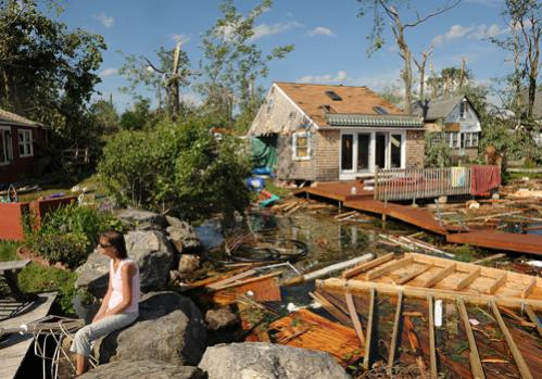 Nicole Labrecque of Kennebunk, ME, visits her friends as she and others survey the damage to homes on Lake Road in Epsom on July 25, 2008.