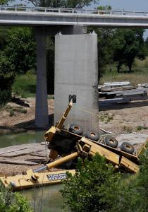 The workers were trying to loosen the joints of a beam, or girder, when another beam also became loose and caused the crane to topple yesterday into the Colorado River, authorities said.