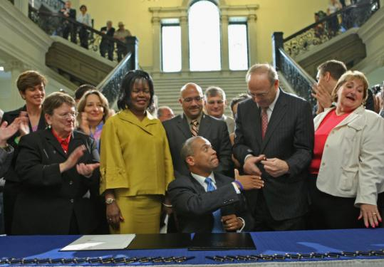 Surrounded by lawmakers, Governor Deval Patrick signed the bill repealing the 1913 law in a ceremony in the State House.