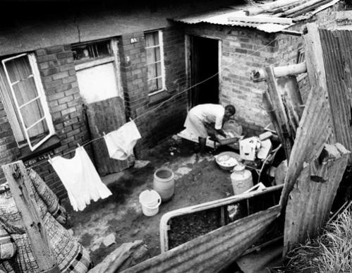 A woman launders clothes by hand outside her brick and tin home in Alexandra on January 24, 1986.