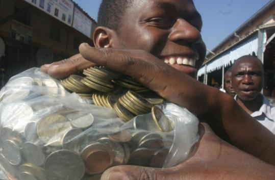 A man carried coins to a Harare bank. Lines grew as overwhelmed tellers counted the reintroduced coins, made obsolete in 2002.