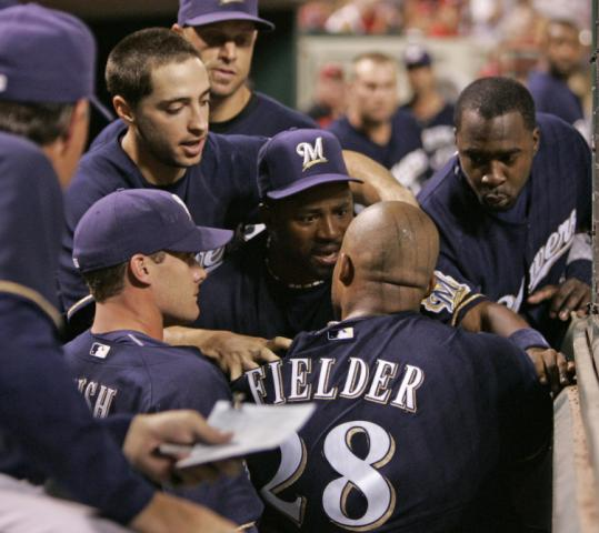 Prince Fielder is held back by his teammates after he had a shoving match with Manny Parra in the Brewers' dugout.