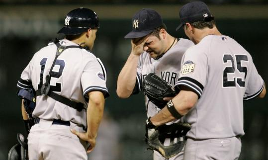 Yankees starter Joba Chamberlain (center) grimaces after suffering a shoulder injury in the fifth inning.