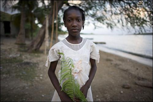 A girl poses for a photo at the Ibo beach, Port-au-Prince, Tuesday, July 8, 2008.