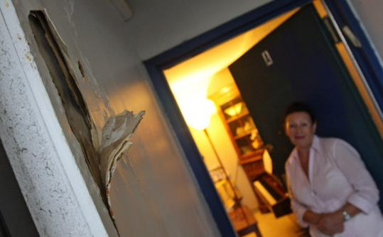 Charlesview resident Raisa Shapiro looks at the peeling wall in her hallway. Says Shapiro, ''The walls are melting.''