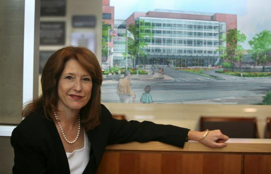 Jeanette Clough, president and CEO of Mount Auburn Hospital, with an architect's rendition of the expanded Stanton Building.