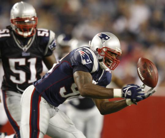 With fellow rookie Jerod Mayo watching, Patriots linebacker Shawn Crable makes a fingertip interception during the first half.