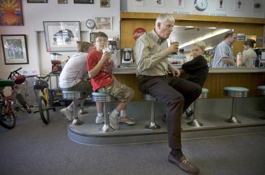Mike Richardson, founder of Dark Horse comics, relaxes at the Main Street Soda Fountain in Milwaukie, Ore., where his company is based. With him are, from left, Jonah Mahoney, 13, Devin Carlson, 12, and Evan Keller, 8.