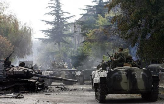 Russian soldiers aboard an armored personnel carrier rolled past a destroyed Georgian tank in the South Ossetian capital of Tskhinvali yesterday.