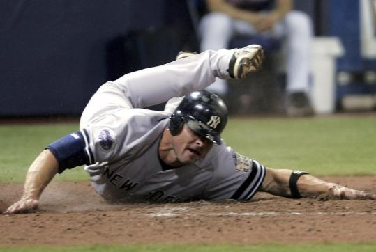 After a long run from first base, Jason Giambi dives and stretches to touch the plate for a Yankees run on Xavier Nady's hit in the fourth inning.