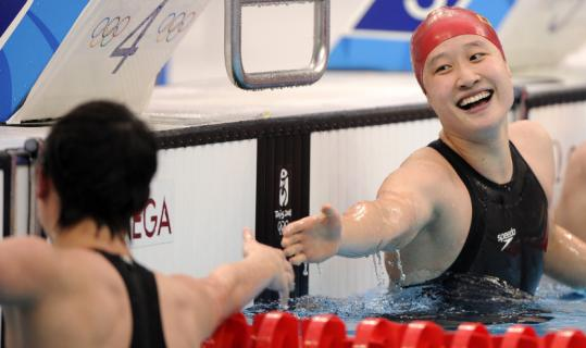 Liu Zige (right) celebrates her 200 butterfly world record with teammate and silver medalist Jiao Liuyang.