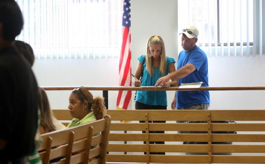 Leah Cappos, 17, got help from her father, Nick, filling out forms to get her driver's license back after a speeding ticket.