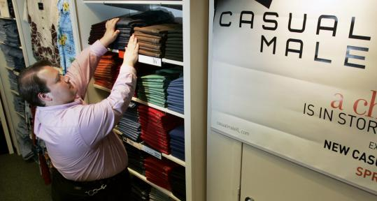 An employee at the Casual Male XL in Downtown Crossing stocks the shelves. Yesterday, the retailer launched its own social networking site.