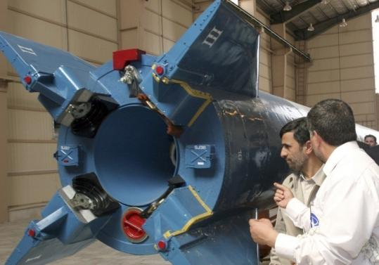 An official spoke to President Mahmoud Ahmadinejad in Tehran yesterday as he looked at a Safir-e Omid rocket.