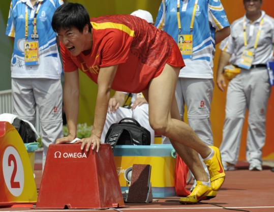 Even before entering the blocks, defending hurdles champ Liu Xiang grimaces while stretching his balky hamstring.