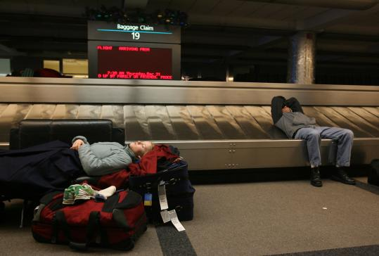 Travelers stranded by bad weather try to get some sleep in the baggage claim area at Denver International Airport.