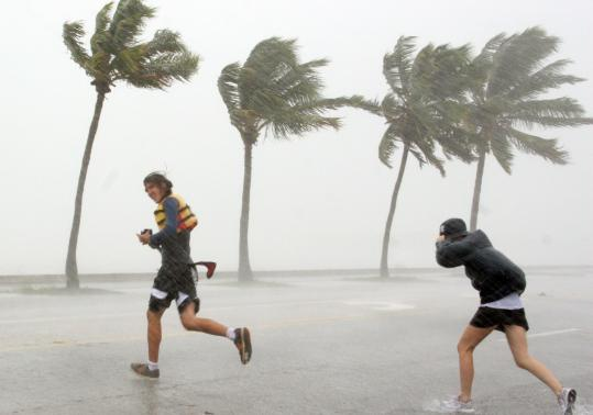 Pedestrians ran across North Roosevelt Boulevard, also known as US Highway One, yesterday in Key West, Fla., as rain bands from Tropical Storm Fay covered the island.