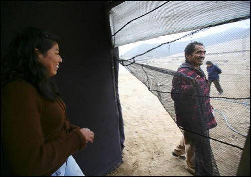 Doris Salazar and Leonidas Yupanqui walk outside a makeshift shelter at the shanty town of Satomi Kataoka, in a desert in Lima, August 19, 2008.