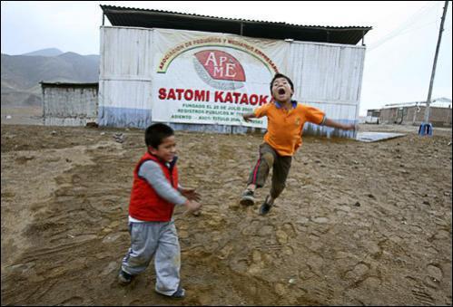 Children play next to a billboard reading 'Satomi Kataoka Association' in Satomi Kataoka.