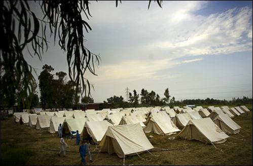 Pakistani men from the Bajur tribal region walk past tents at a relief camp at a school compound in Nowshera district near Peshawar, Pakistan on Wednesday, Aug. 20, 2008.