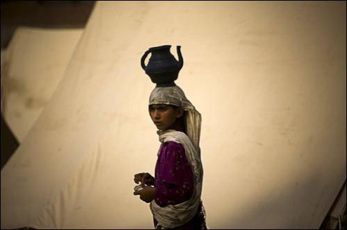 A Pakistani girl from the Bajur tribal region carries a pot with water on her head at a relief camp school compound in Nowshera district near Peshawar, Pakistan on Wednesday, Aug. 20, 2008.