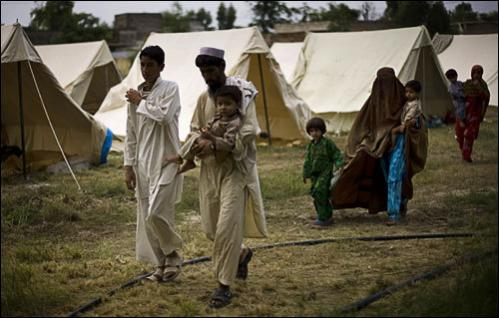 Pakistani people from the Bajur tribal region arrive at a relief camp school compound in Nowshera district near Peshawar, Pakistan on Wednesday, Aug. 20, 2008.