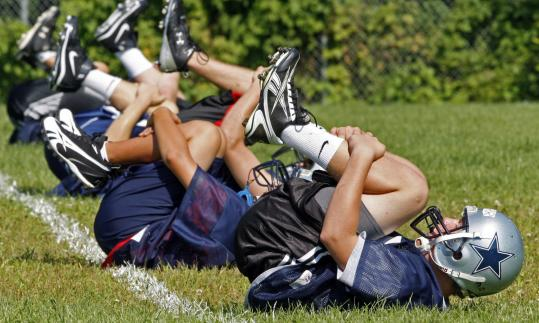 The Hamilton-Wenham High School football team works out. The school's $969 student fee to play football is the highest in the region.