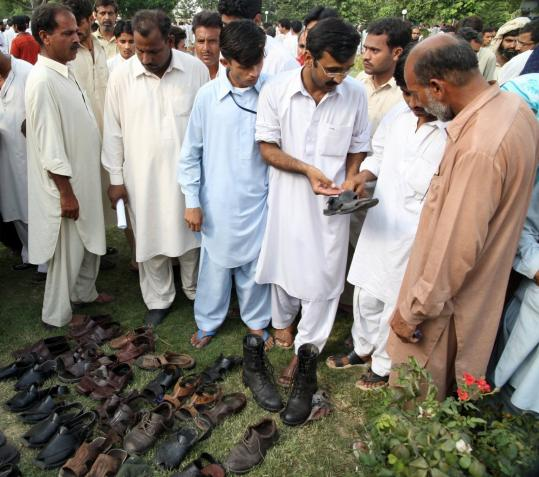 Pakistanis identified the shoes of their relatives yesterday after a suicide attack on an arms factory in Wah, about 20 miles west of Islamabad. Officials said 59 workers died and 70 others were injured in two explosions that occurred during a shift change