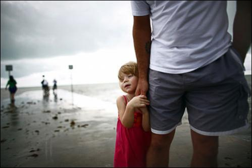 Gigi Gordon stands with her father on a pier during a lull in Tropical Storm Fay August 18, 2008 in Key West, Florida.