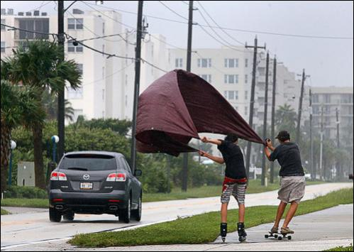 George Torzsa, 15, right, and Patrick Fuzzard, 15, use a tarp and wind from Tropical Storm Fay to power their skateboard and inline skates down Atlantic Avenue in Ponce Inlet, FL Wednesday, Aug. 20, 2008. The pair hopped a city bus and traveled 3 miles north of their homes to experience the thrill ride back.