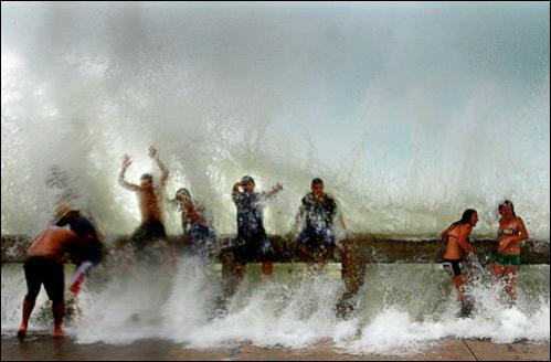 Storm enthusiasts get soaked by waves crashing against the pier in Key West, FL during Tropical Storm Fay on Monday, Aug. 18, 2008.
