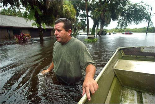 Tony Tescher pulls a boat to a friend's home to collect food. The home was badly damaged from flood waters and they were taking the food to his grandmother's dry home on the other side of S. 25th St.