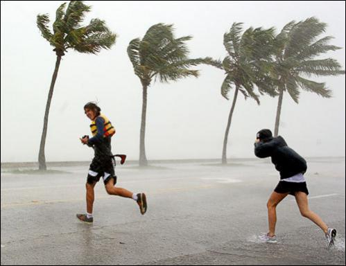 Pedestrians run across North Roosevelt Boulevard, also known as U.S. Highway One, Monday August 18, 2008, in Key West, FL, as rain bands from Tropical Storm Fay cover the island.
