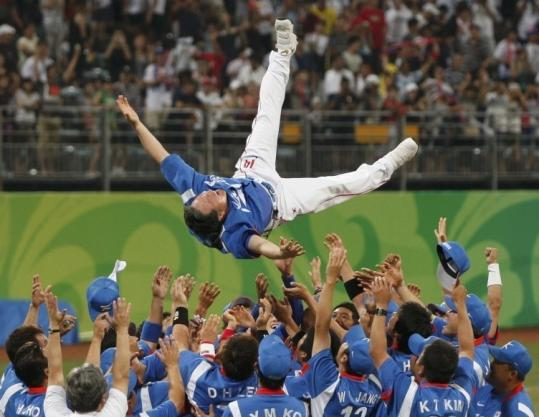 South Korean players play short toss, heaving manager Kim Kyung Moon after winning the gold medal in dramatic fashion.