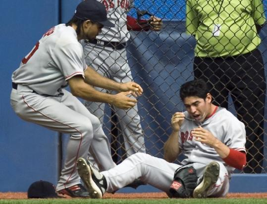 Red Sox center fielder Coco Crisp rushes to the aid of right fielder Jacoby Ellsbury after Ellsbury crashed into the wall while chasing down a long fly ball by Adam Lind in the fourth inning.