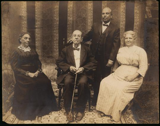 A family photo taken between 1913 and 1918, in Cohasset. From left: Annie Washington, John Washington, their son James (standing), and his wife, Catherine.