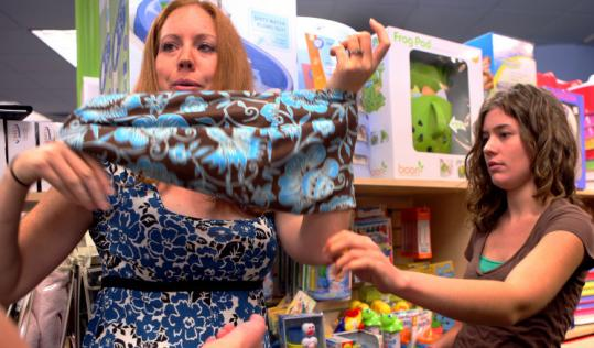 Salesperson Mara Beier (right) helped Stacey Lightbody as she tried on a baby sling at Magic Beans in Brookline.