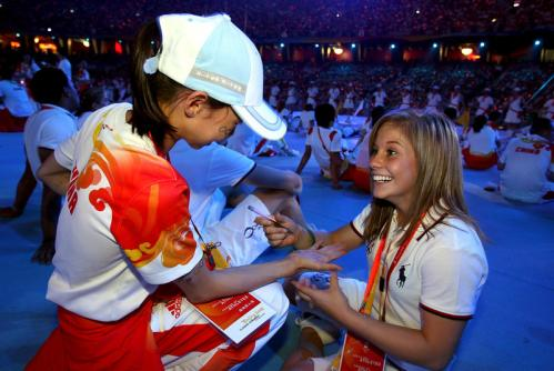 Shawn Johnson of the United States gymnastics team signs an autograph during the Closing Ceremony.
