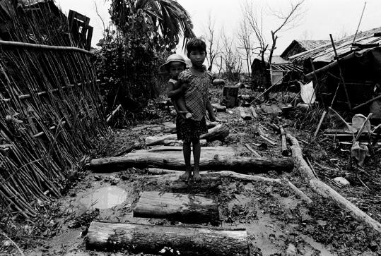 Amid destruction and mud, children walked in a village in Labutta Township. About 50 village residents died in the cyclone.