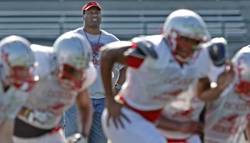 Catholic Memorial volunteer assistant coach and former Patriots lineman Brent Williams watches his son, Brennan (foreground right), run at practice.