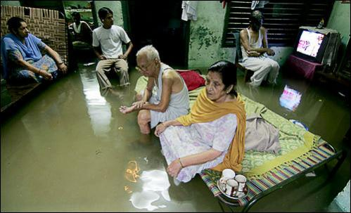 An Indian family sits in their waterlogged home in Amritsar, August 13, 2008, after a heavy downpour of monsoon rain in the northern Indian city. Heavy downpours continue to cross northern India as the south-west monsoon travels across the Indian subcontinent.