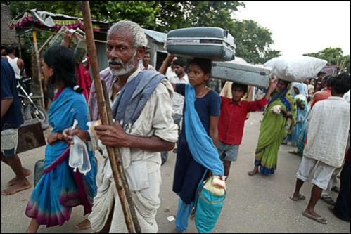 Indian villagers walk along India's National Highway 57A after they were rescued from floodwaters in the Sursur area in Araria district, some 420 kms northeast of Patna on August 27, 2008. Indian emergency services rushed supplies to 2.5 million people marooned after heavy monsoon rains caused a river to shift its course, a minister said.