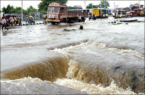 Commuters wade through flood water in Hyderabad, India, Tuesday, Aug. 26, 2008. India's monsoon season, which lasts from June to September, brings rain vital for the country's farmers but also massive destruction. Floods, mudslides, collapsing houses and lightning strikes kill hundreds of people every year.