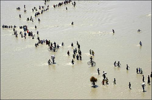 People seek refuge from flood waters in east Nepal August 24, 2008. The Koshi river breached its banks ten days ago on the border with Nepal, flowing through a channel it had previously abandoned. At least 46 people are reported to have died in the floods, as troops and air force helicopters rushed to help police in the rescue operation.