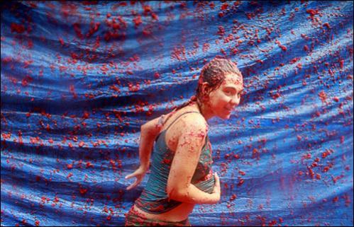A reveleler runs carrying tomatoes during the Tomatina in Bunol, Spain, Wednesday, Aug. 27, 2008.